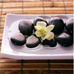 Orchid wedding centerpiece with black pebbles on a white square plate with bamboo mat.
