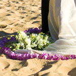 A string of purple orchids surrounding the bride and groom on the sand at a beach wedding.
