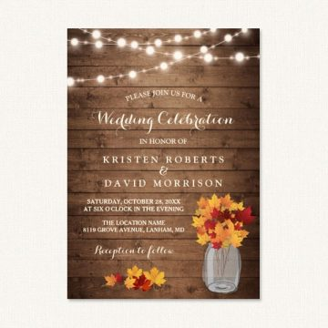 Autumn themed wedding invitations with string lights, wood grain and fall leaves in jar.