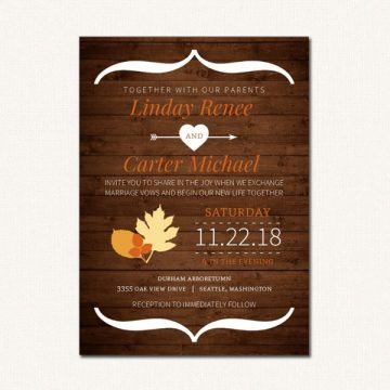 Autumn wedding invitation with fall leaves and wood grain background.