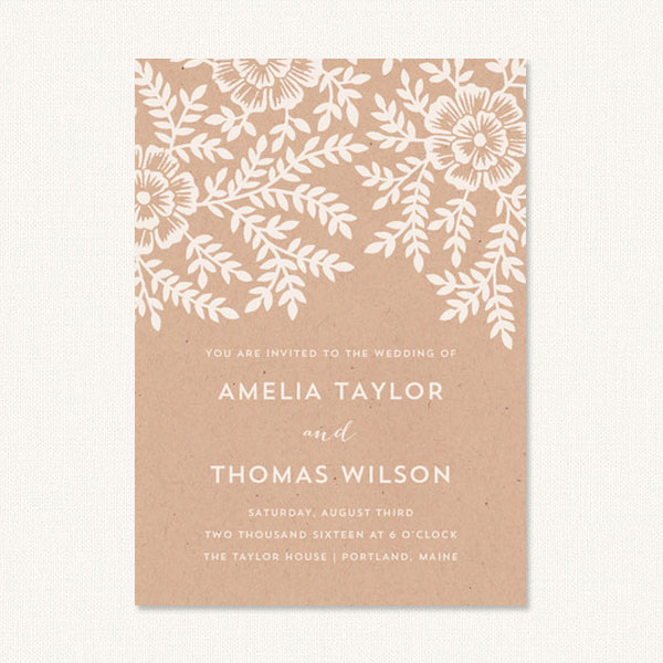 Floral rustic wedding invitations with white leaf and flower design on a kraft background.