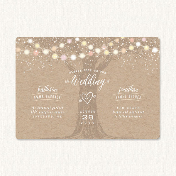 Garden light wedding invitations with a tree in the center, heart and arrow carving and colored string lights.