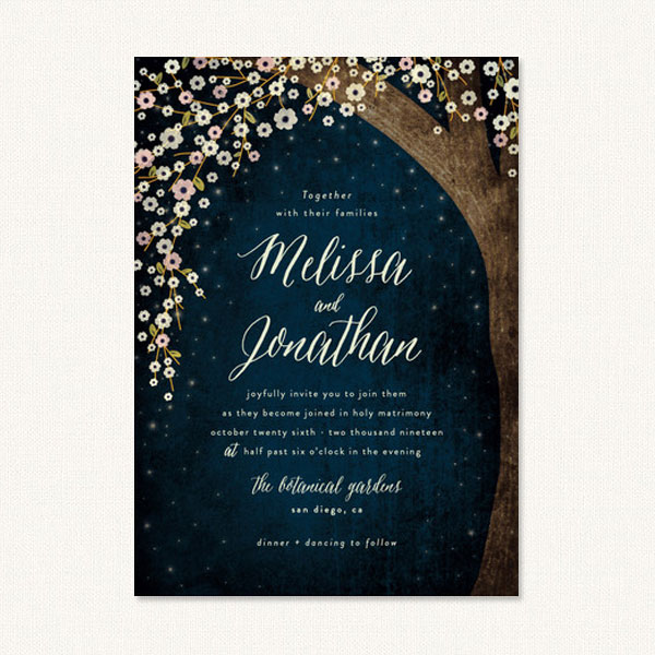 Tree themed wedding invitations with a flowering tree against a starry evening sky.