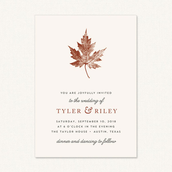 Unique fall wedding invitations with leaf print on cream background.