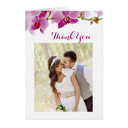 Wedding thank you card with thank you message in script font and bride and groom photo on the front.