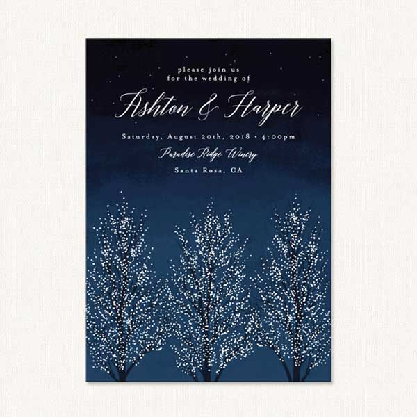 Winter themed wedding invites with trees covered in delicate snow.